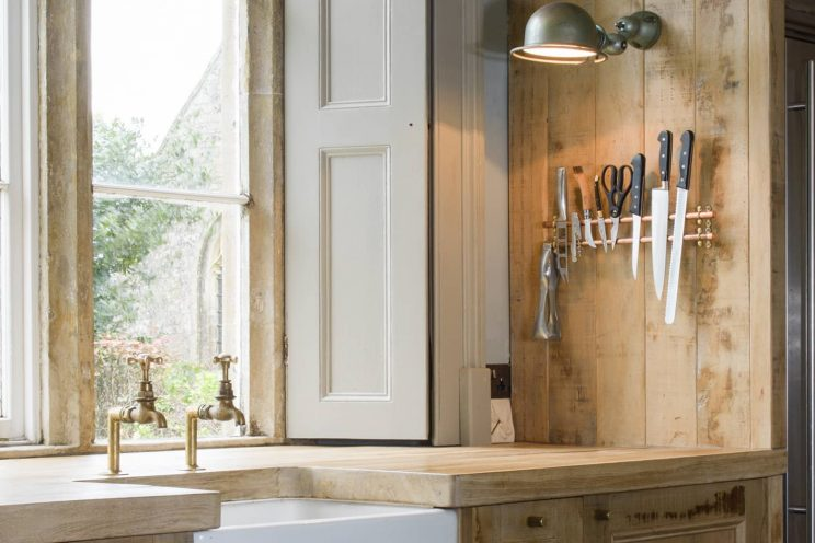 Rustic oak kitchen with large stainless steel fridge freezer and large sunken ceramic sink. designed by Mia Marquez