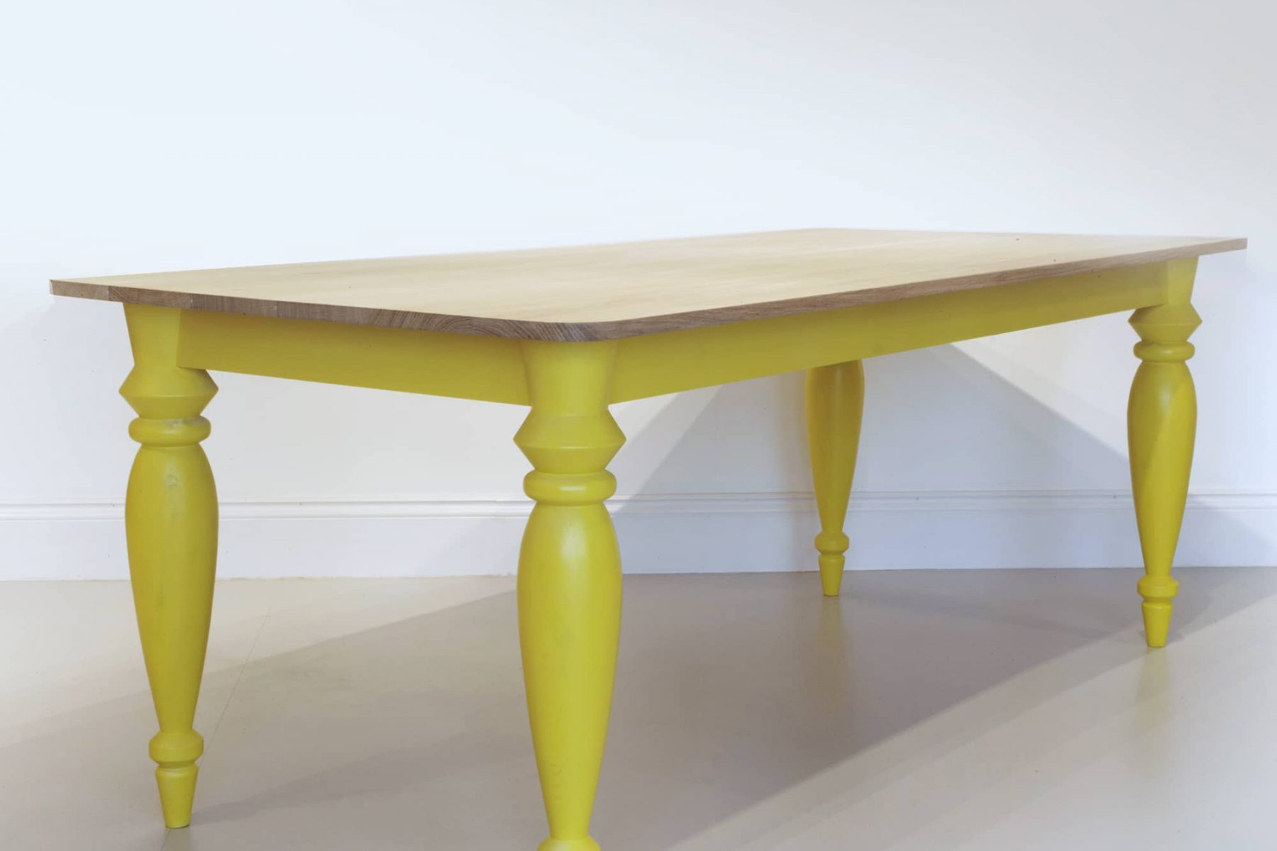 Contemporary wooden kitchen table with yellow legs