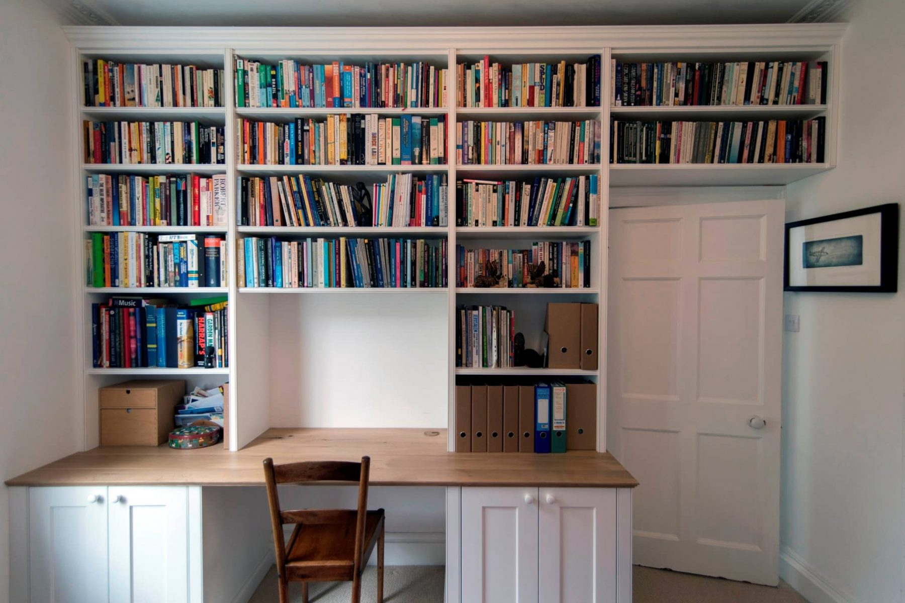 Study room with large wall length fitted bookcases