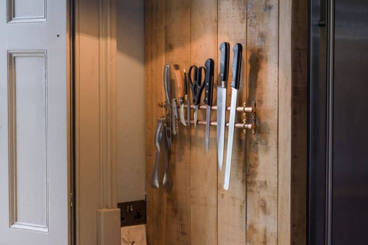 Rustic sustainable kitchen with magnetic knife storage designed by Mia Marquez