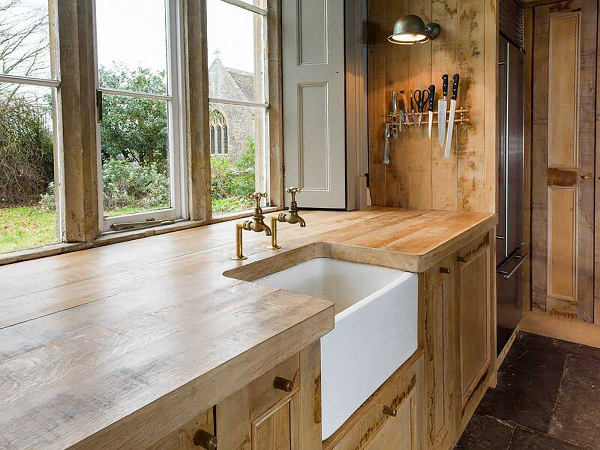Rustic wood kitchen with white basin sink designed by Mia Marquez