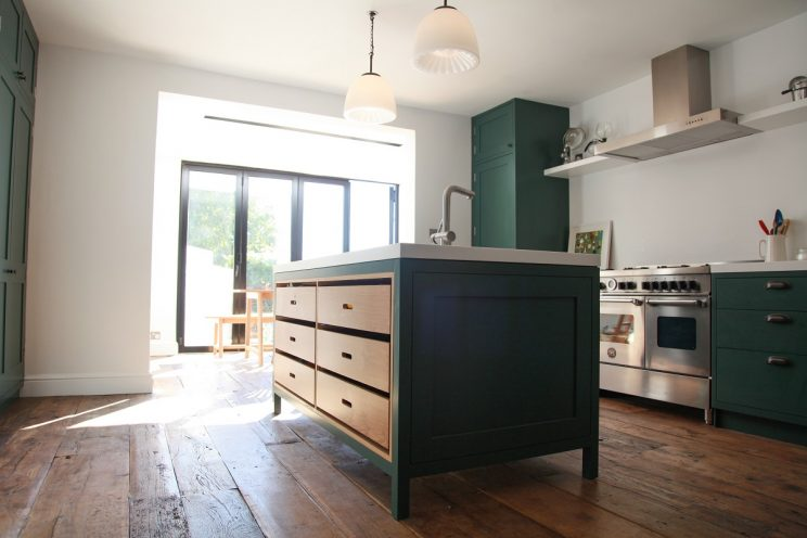 Green shaker kitchen with wooden flooring