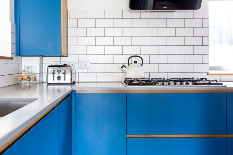 Electric blue kitchen with Corian worktop and white tiles