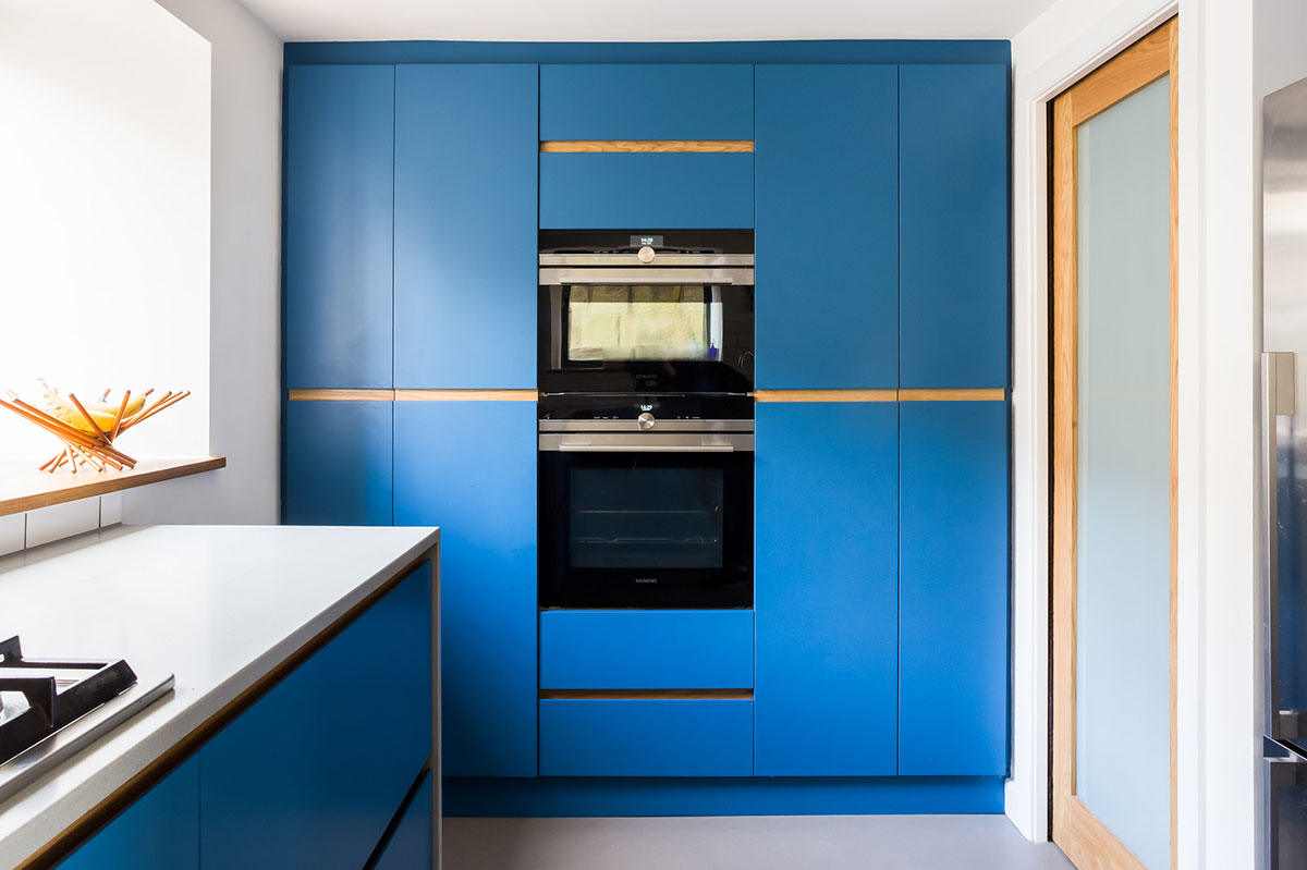 Electric blue modern kitchen large larder with double tier cooker
