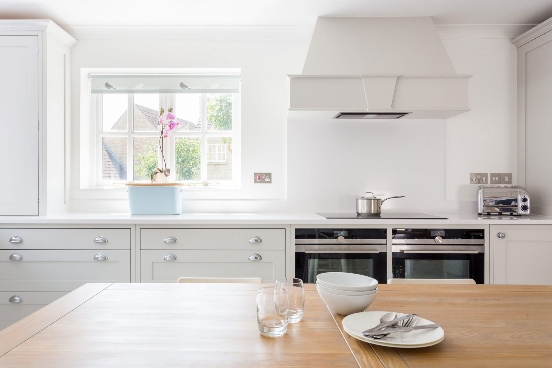 Contemporary white Shaker kitchen in Bath with bespoke cooker hood