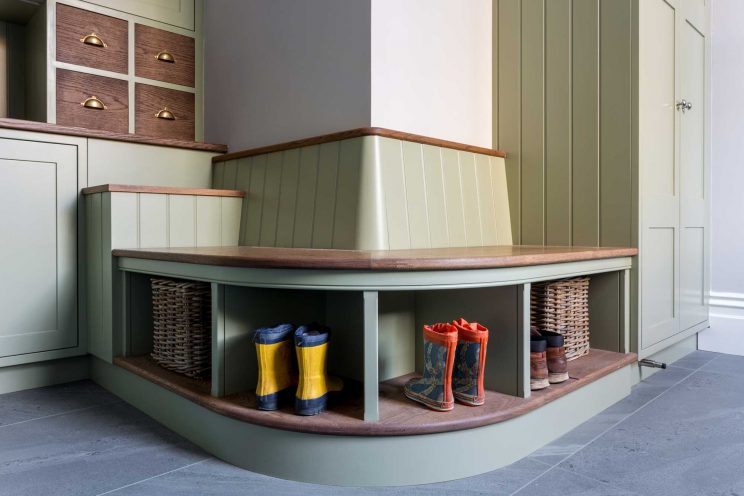 Curved seating area in boot room with wooden wall panelling