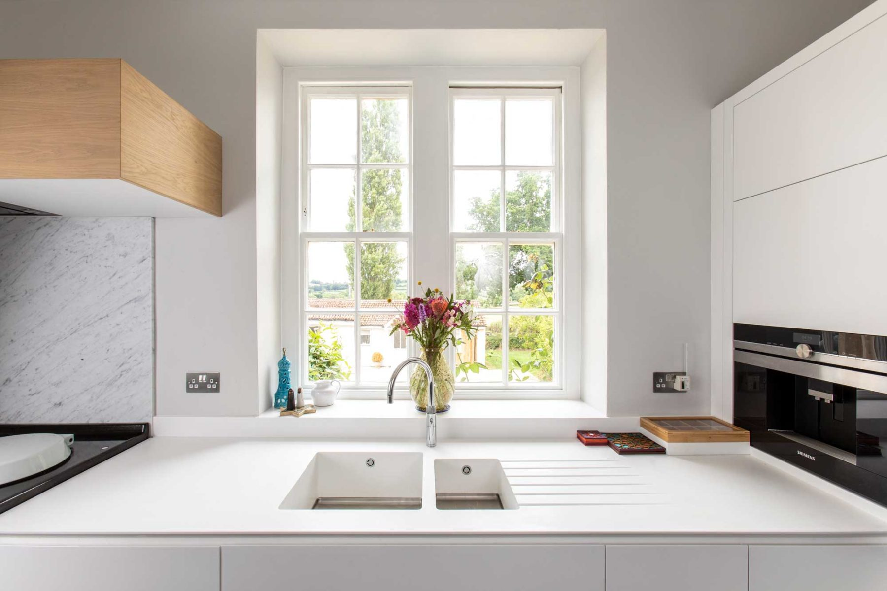 Modern white and blue kitchen with submerged Corian sink