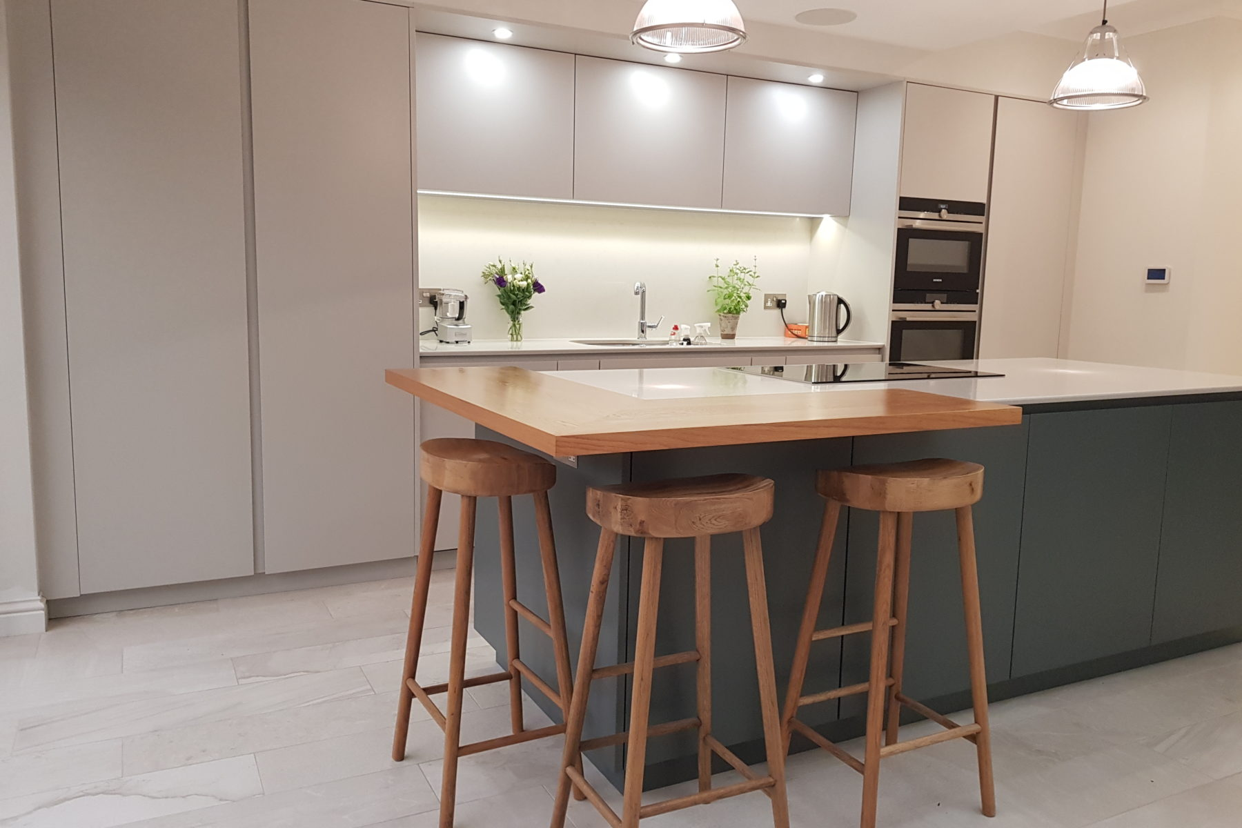 Contemporary slab door kitchen with wooden stools